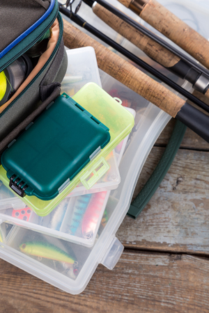 wobler: fishing tackles and baits in box and bag on wooden boards background for outdoor active business