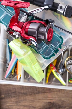 wobler: fishing reel and rod on boxes with different lures and wobblers for outdoor active business