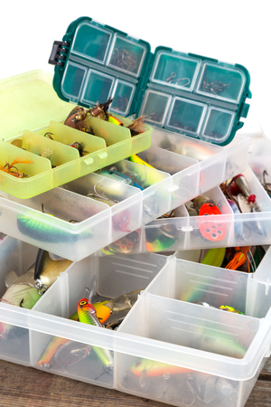 wobler: different fishing lures and baits in plastic box on wooden boards background for outdoor active business