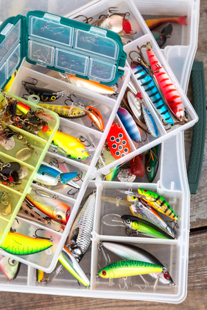 diferent: different fishing lures and baits in boxes on wooden boards background for outdoor active business