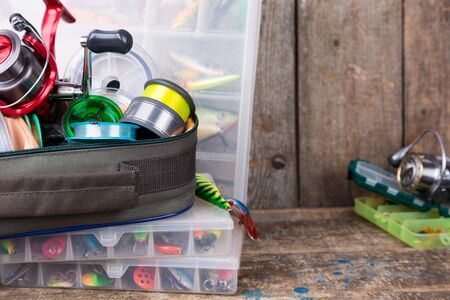 wobler: fishing tackles, lures and baits in boxes on wooden timbers background for outdoor active business Stock Photo