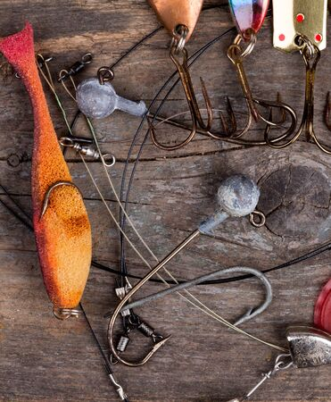 jigging: different fishing tackles and spoon on wooden board background. Concept design for freshwater outdoor active business company.