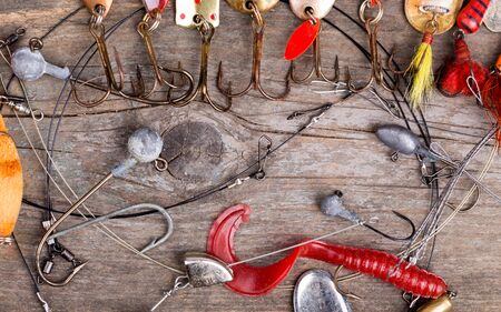 wobler: different fishing tackles and spoon on wooden board background. Concept design for freshwater outdoor active business company.