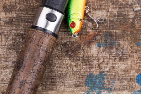 closeup cork handle of fishing rod with lure on wooden board background. Concept design for freshwater outdoor active business company.