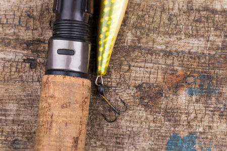 wobler: closeup cork handle of fishing rod with lure on wooden board background. Concept design for freshwater outdoor active business company.