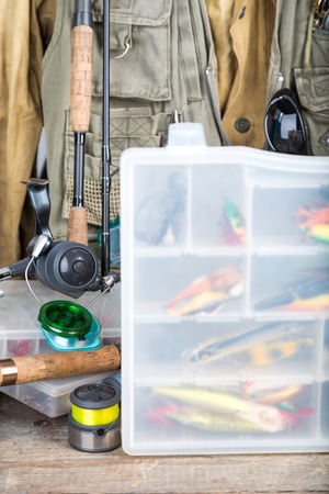 wobler: fishing baits in blure storage box with background fishing tackles, vest, rubber boots and wooden boards. design background for outdoor  advertisement, flayer etc.