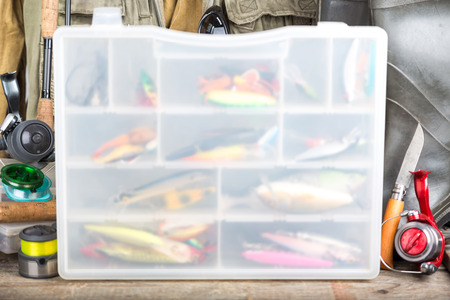 plummet: fishing baits in blure storage box with background fishing tackles, vest, rubber boots and wooden boards. design background for outdoor  advertisement, flayer etc.