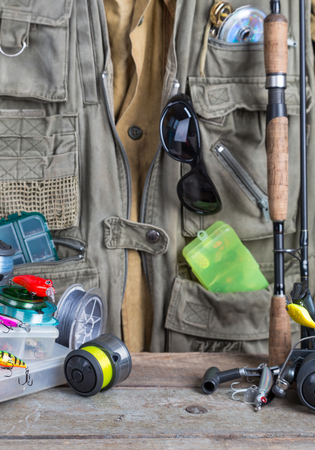 wobler: fishing tackles with fishing vest and wooden boards. design background for outdoor  advertisement, flayer etc. Stock Photo