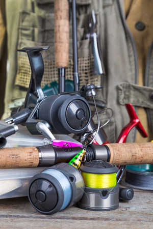 wobler: fishing tackles with fishing vest, boots and wooden boards. design background for outdoor  advertisement, flayer etc.