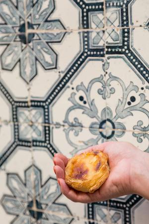 nata: Traditional Portuguese egg tart pasty cake dessert Pasteis de nata in women hand. On background azulejo in Lisbon, Portugal.