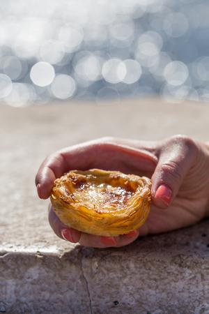 nata: Traditional Portuguese egg tart pasty cake dessert Pasteis de nata in women hand. On background promenade in Lisbon, Portugal.