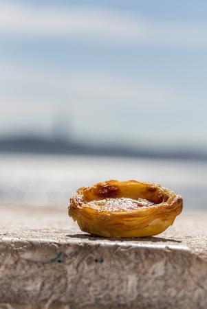 nata: Traditional Portuguese egg tart pasty cake dessert Pasteis de nata on background seafront in Lisbon, Portugal.