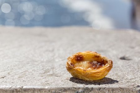 Traditional Portuguese egg tart pasty cake dessert Pasteis de nata on background seafront in Lisbon, Portugal.