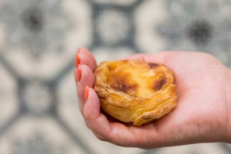 Traditional Portuguese egg tart pasty cake dessert Pasteis de nata in women hand. On background azulejo in Lisbon, Portugal.