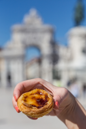 Traditional Portuguese egg tart pasty cake dessert Pasteis de nata in women hand. On background attractions in Lisbon, Portugal.