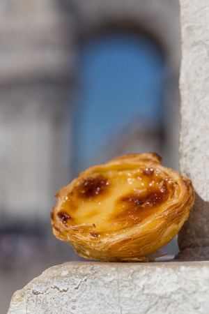Traditional Portuguese egg tart pasty cake dessert Pasteis de nata on background attractions in Lisbon, Portugal.