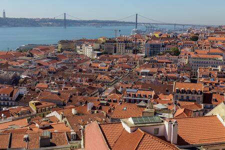 view on travel city Lisbon from top place of castle sao jorge. roofs, river tejo, brige 25 april, ships in summer day. Stock Photo