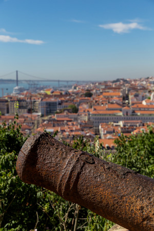 river trunk: view on travel city Lisbon with old metal cannon trunk from top place of castle sao jorge. roofs, river tejo, brige 25 april, ships in summer day. Stock Photo