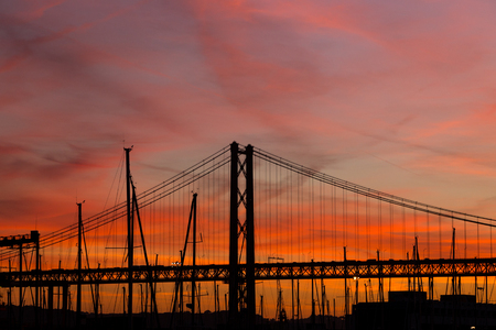 sunset landscape in city with bridge and yachts in red, orange colors