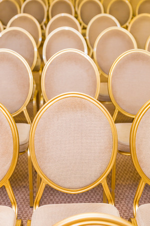 rank of empty chairs in vintage style with round seat back in conference room Stock Photo
