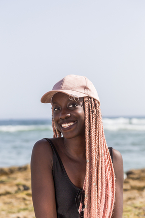hate: African young girl in a black bathing suit and cap with long pink pigtails posing in the background of the beach and ocean