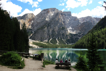 Four tourists sit on a bench near the Lake Braies (Lago di Braies) and admire the amazing view of Dolomites Alps