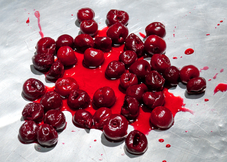 sour cherry: Splashed sour cherries on metallic surface sour cherry fruits pattern Stock Photo