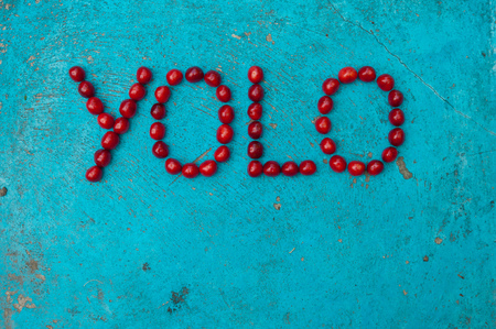 once person: Cherries arranged to form the word YOLO on textured blue background