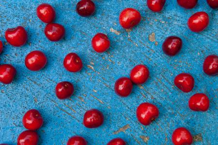 textrured: Arrangement of ripe cherries on blue textrured background, cherry pattern