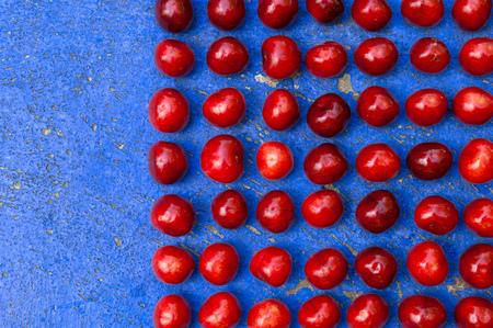 textrured: Square arrangement of ripe cherries on blue textrured background, cherry pattern