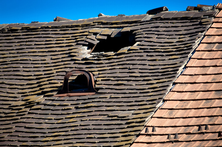 Old damaged tiled roof with broken tiles and a hole on the roof Stock Photo