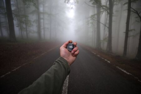 Survior young adult hiker searching the direction to home with navigational compass in the foggy forest.
