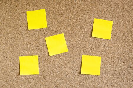 Corkboard with yellow sticky notes Stock Photo
