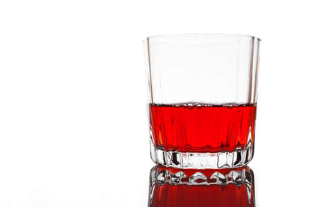 Glass of red juice on white