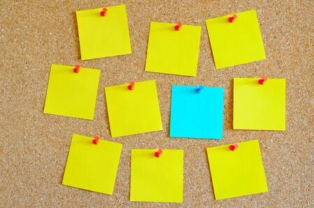 Cork board with multiple yellow and one cyan post-it Stock Photo - 17580493