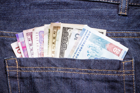 bolsa dinero: Pocket money various currency bills in jeans. Foto de archivo