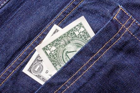 money in the pocket: Pocket money. One dollar bill in blue jeans.
