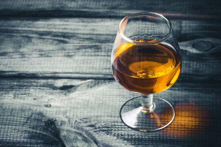 Cognac glass on grunge black wooden bar.