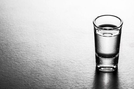 crystal glass: Vodka shot glass isolated on white with reflection.