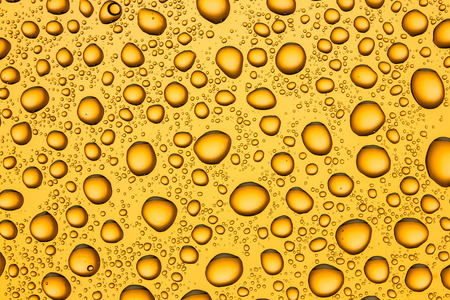 Water drops on yellow glass surface texture.