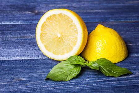 Yellow lemon with mint on blue grunge wooden table.