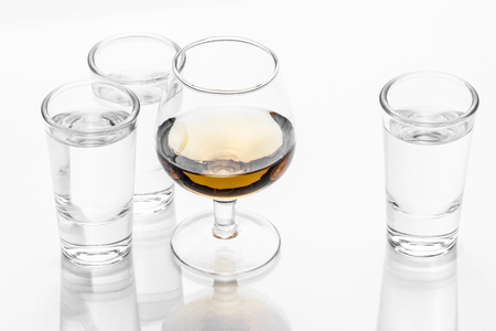 Vodka shot glass and cognac glass isolated on white.
