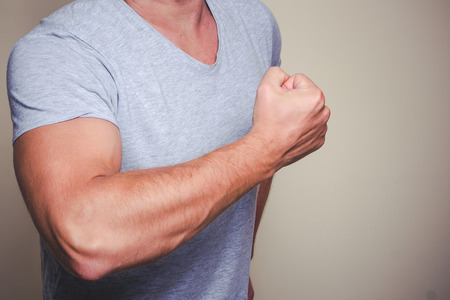 Well build young man. Chest in gray shirt and muscled hands. Stock Photo