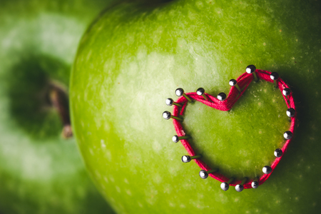 hilo rojo: Heart shape made with red thread and pins on green apple. Foto de archivo