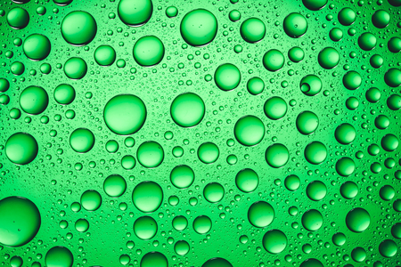 fizz: Green water drops on glass surface texture.