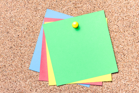 Green, yellow, red and blue notes pined to cork board. Empty reminder cards.