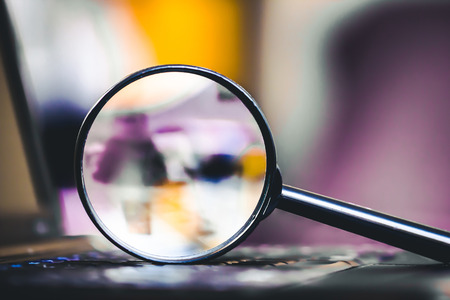 Search technology background. Magnifying glass on computer keyboard with shallow depth of field and blurred colors inside.