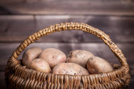 Potatoes in basket on wooden vintage background. Stock Photo