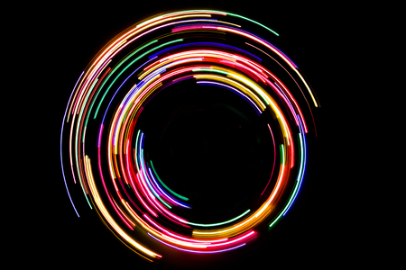 Abstract rotating neon lights texture with black space. Imagens