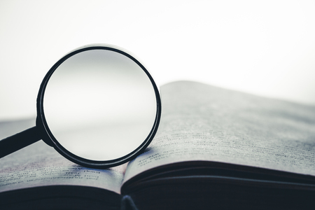 Magnifying glass on the open book background. Empty copy space inside. Stockfoto